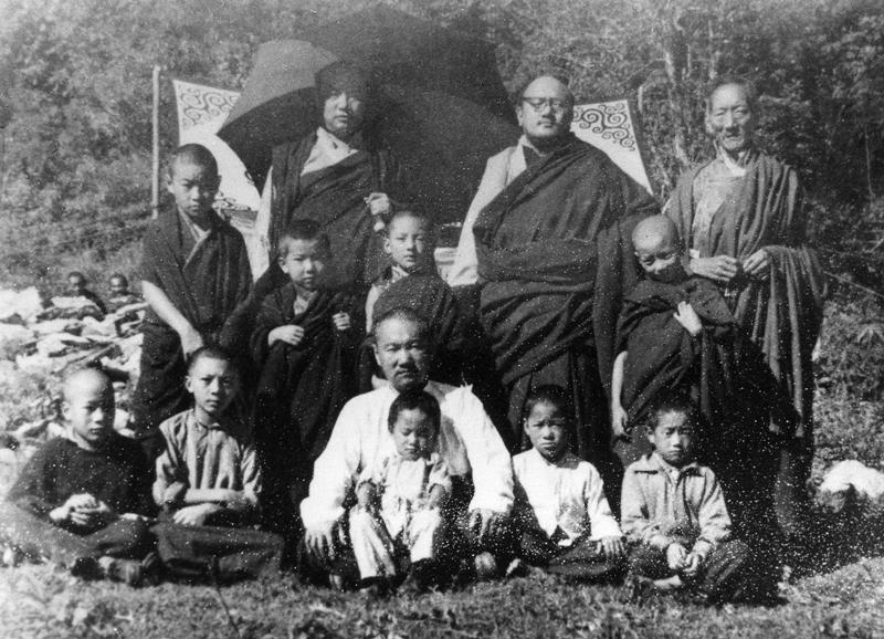 En haut, de gauche à droite : le XVIe Karmapa, Dzogchen Pönlop Rinpoché, Kalu Rinpoché. Au milieu, de gauche à droite : Tendzin Chöny, Kongtrul Rinpoché, Shamar Rinpoché, Gyalsé Tülku. En bas, de gauche à droite : Tsültrim Namgyal, Jigmé Rinpoché, Gyalkar Gönam, Tashi Namgyal, Khenpo Chödrak, Gyurmé Tsültrim. Photographie prise le premier jour de la cérémonie d'inauguration des travaux à Rumtek, au début des années 60